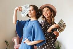 Emotional young women indoors holding money. Stock Photo
