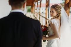 Emotionale blonde Braut, die Bräutigam, elegante Braut lächelt u. betrachtet Lizenzfreies Stockfoto