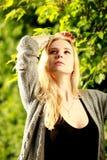 Emotionale Blondine im sonnigen Wald, schauend auf Himmel, übergeben oben Stockbild
