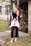 Emotionale Blondine in Schwarzem und in rosa mit den geschlossenen Augen, die einen tr halten Lizenzfreies Stockfoto
