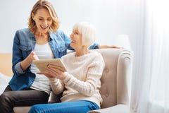 Emotionale Frau, die beim Zeigen auf das lustige alte Foto überrascht schaut stockbilder