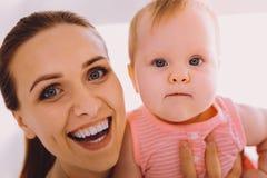 Emotionale Frau, die ihr angenommenes Baby hält und glücklich sich fühlt Lizenzfreies Stockbild