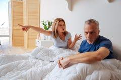 Emotionale Frau, die an ihrem Ehemann nach Verrat schreit stockbild