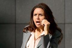 Emotionale Frau, die an ihrem Handy spricht Lizenzfreies Stockfoto