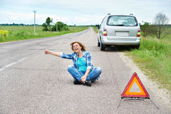 Emotionale Frau, die oben auf Straße nahe Rettungszeichendaumen sitzt Stockbild