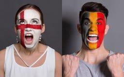 Emotionale Fußballfans mit gemalten Flaggen auf Gesichtern lizenzfreie stockbilder
