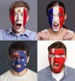 Emotionale Fußballfans mit gemalten Flaggen auf Gesichtern stockbild