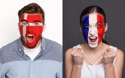 Emotionale Fußballfans mit gemalten Flaggen auf Gesichtern stockfotografie