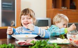 Emotionale glückliche Kinder, die bei Tisch essen stockfotografie