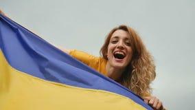 Emotionale junge Frau, die blaue und gelbe ukrainische Flagge über dem Himmelhintergrund hält stock video