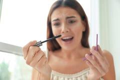 Emotionale junge Frau, die zuhause Wimperntuschenbürste mit den Wimpern hält lizenzfreie stockfotos