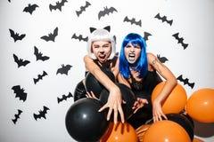 Emotionale junge Frauen in Halloween-Kostümen Stockfotografie