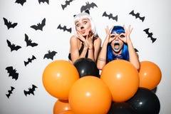 Emotionale junge Frauen in Halloween-Kostümen Lizenzfreie Stockbilder