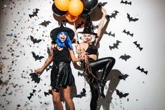 Emotionale junge Frauen in Halloween-Kostümen Stockbild