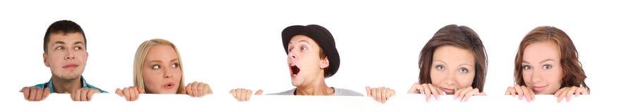 Emotionale junge Leute hinter weißer Anschlagtafel Stockbilder