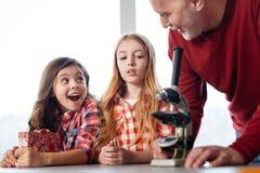 Emotionale neugierige Kinder faszinierten über die Anwendung eines Mikroskops stockfoto