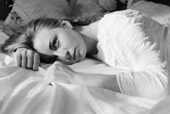 Emotionale schöne blonde junge Frau, die im Bett liegt Stockfoto