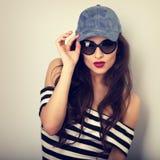 Emotionale sexy junge Frau in Sonnenbrille und in blauer Baseballmütze p Stockfotografie
