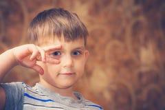 Emotionale Shows eines Jungen stark ein anderes Gesicht zur Kamera stockbild