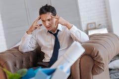 Emotionaler arbeitsloser Mann, der beim zu Hause sitzen verrückt geht stockbild