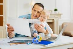 Emotionaler Arbeitsvater, der einem kleinen Baby seine Grafiken zeigt Lizenzfreies Stockbild