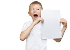 Emotionaler blonder Junge in einem weißen Hemd mit einem grauen Blatt Papier für Anmerkungen über einen weißen Hintergrund Stockfoto