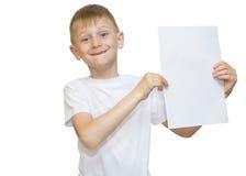 Emotionaler blonder Junge in einem weißen Hemd mit einem grauen Blatt Papier für Anmerkungen über einen weißen Hintergrund Stockfotografie