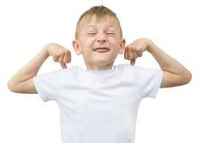 Emotionaler blonder Junge in einem weißen Hemd mit einem grauen Blatt Papier für Anmerkungen über einen weißen Hintergrund Lizenzfreies Stockfoto