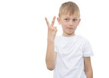 Emotionaler blonder Junge in einem weißen Hemd mit einem grauen Blatt Papier für Anmerkungen über einen weißen Hintergrund Lizenzfreie Stockfotografie