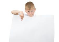Emotionaler blonder Junge in einem weißen Hemd mit einem grauen Blatt Papier für Anmerkungen über einen weißen Hintergrund Lizenzfreie Stockfotos