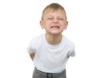 Emotionaler blonder Junge in einem weißen Hemd mit einem grauen Blatt Papier für Anmerkungen über einen weißen Hintergrund Lizenzfreies Stockbild