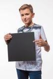 Emotionaler blonder Junge in einem weißen Hemd mit einem grauen Blatt Papier für Anmerkungen Stockfoto