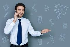 Emotionaler eleganter Mann, der bei der Unterhaltung am Telefon glücklich schaut Lizenzfreie Stockfotos