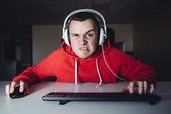 Emotionaler Gamer im Kopfhörerhaus, welches das Spiel auf Ihrem Computer spielt Er ist verärgert, weil verloren lizenzfreie stockfotos