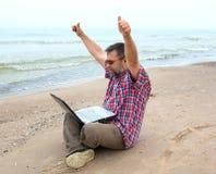 Emotionaler Geschäftsmann mit Laptop auf dem Strand Stockfotografie