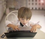 Emotionaler kleiner Junge, der Laptop verwendet Stockbild