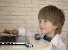 Emotionaler kleiner Junge, der Laptop verwendet Lizenzfreie Stockfotografie