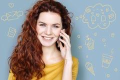 Emotionaler lächelnder Blogger bei der Unterhaltung am Telefon Stockfotografie