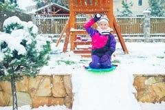 Emotionaler Mädchenspielschnee-Ballkampf des schulpflichtigen Alters im Winteryard Stockfotos