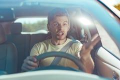 Emotionaler Mann, der beim Fahren nahe gefährlichem Fahrer wütend sich fühlt lizenzfreies stockfoto