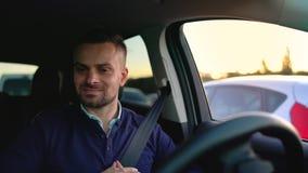 Emotionaler Mann, der in innovatives automatisiertes Auto unter Verwendung der Selbstparkautomatischen kurssteuerung für das Park stock video