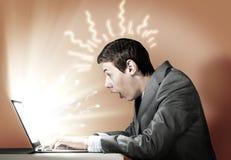 Emotionaler Mann, der Laptop verwendet Stockfotos