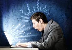 Emotionaler Mann, der Laptop verwendet Stockbilder