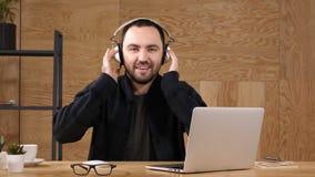 Emotionaler Mann mit hörender Musik der Kopfhörer und Schauen zur Kamera stock video footage