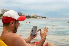 Emotionaler Mann mit Telefon in seiner Hand auf Strand Stockfotos