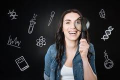 Emotionaler Student, der eine Lupe lacht und hält Lizenzfreie Stockfotos