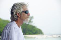 Emotionaler u. durchdachter schauender Ozean des alleingefühls des älteren Mannes lizenzfreies stockfoto
