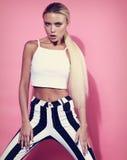 Emotionales blondes dünnes Modell der Leidenschaft mit dem langen Haar, das im stri aufwirft Stockfoto
