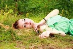 Emotionales blondes, Träumen, in camera schauend und liegen auf den gras Stockfoto