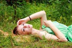 Emotionales blondes, träumend und schauen im Himmel und liegen auf dem gra Stockfotos